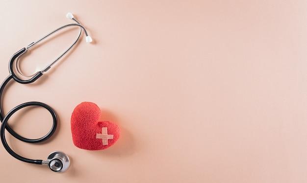 Vue de dessus du stéthoscope docteur et coeur rouge sur fond pastel