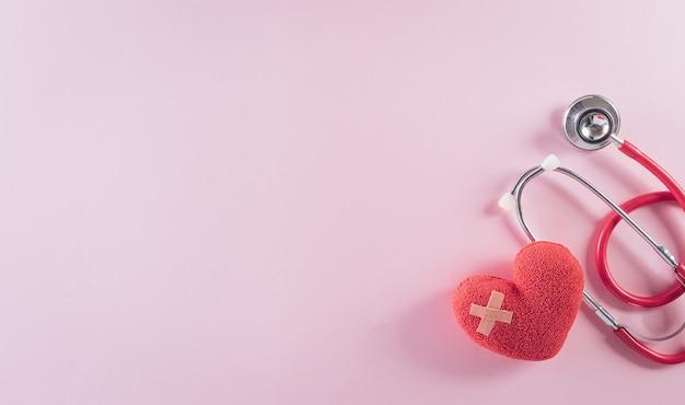 Vue de dessus du stéthoscope docteur et coeur rouge sur fond rose