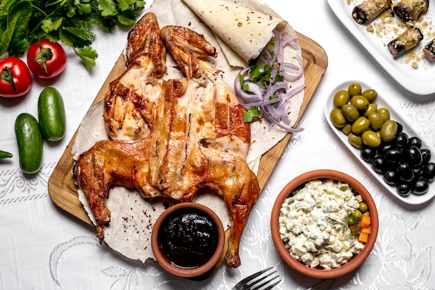 Vue de dessus du tabac sur du pain pita aux oignons et sauce avec salade et olives