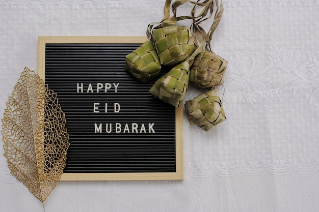 La vue de dessus du tableau des lettres dit happy eid mubarak et de la nourriture traditionnelle pendant la célébration du baran appelée ketupat avec espace de copie
