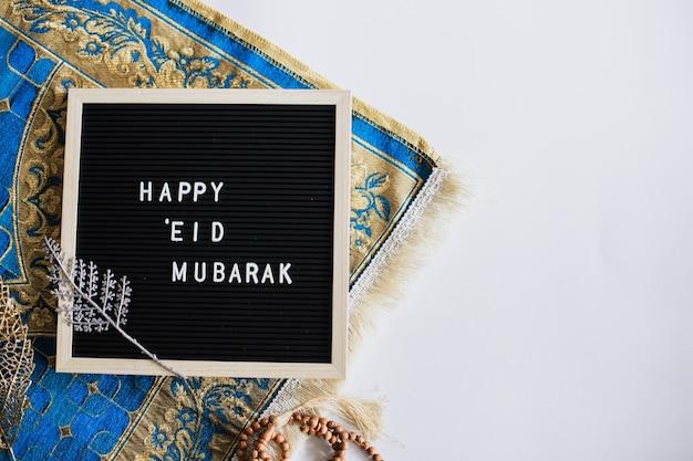 La vue de dessus du tableau des lettres dit happy eid mubarak sur le tapis de prière avec espace de copie