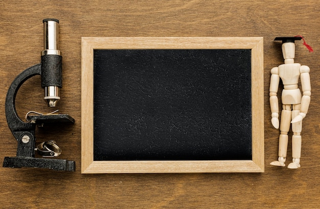Vue de dessus du tableau noir avec microscope et figurine en bois