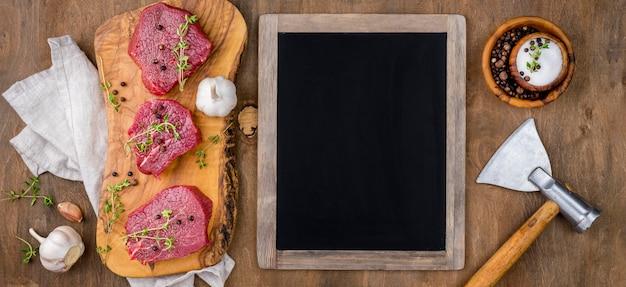 Vue de dessus du tableau noir avec de la viande et de l'ail
