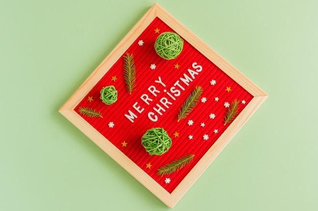 Vue de dessus du tableau avec texte joyeux noël, flocons de neige en sucre et boules de ratang vertes sur vert. carte de voeux festive.