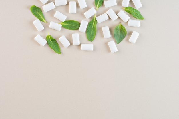 Vue de dessus du tas de gencives blanches avec des feuilles de menthe sur la crème.