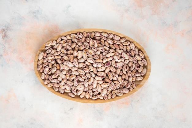 Vue de dessus du tas de haricots dans une assiette en bois sur une table blanche.