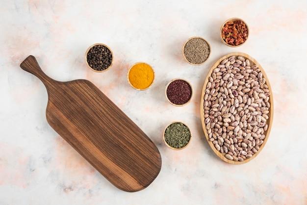 Vue de dessus du tas de haricots avec divers types d'épices et planche à découper en bois.