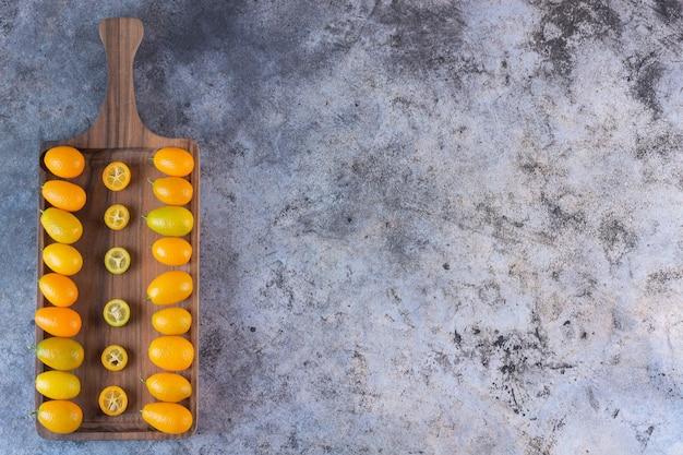 Vue de dessus du tas de kumquats sur planche de bois.