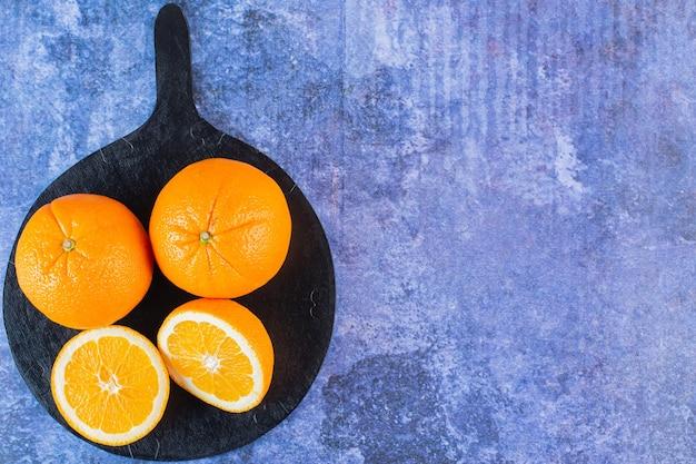 Vue de dessus du tas d'orange sur planche de bois sur bleu.