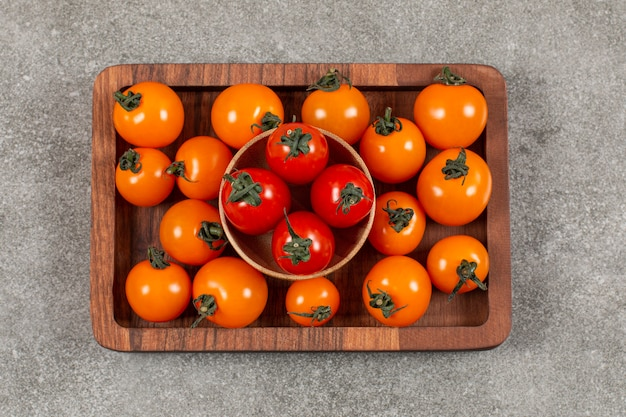 Vue de dessus du tas de tomates cerises sur plaque en bois.