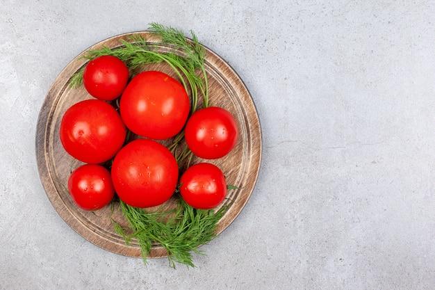 Vue de dessus du tas de tomates rouges fraîches sur planche de bois.