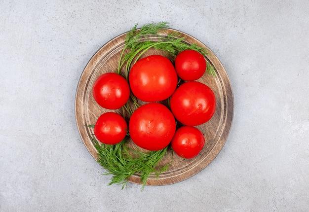 Vue de dessus du tas de tomates rouges sur planche de bois.