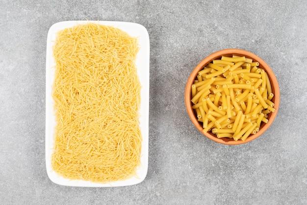 Vue de dessus du tas de vermicelles sur assiette et pâtes dans un bol.