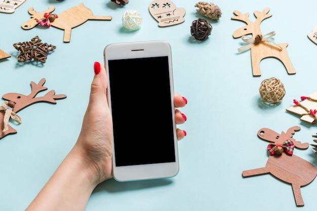 Vue de dessus du téléphone dans une main féminine sur bleu festif