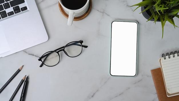 Vue de dessus du téléphone intelligent avec écran vide, verres, tasse à café et ordinateur portable sur fond de marbre.