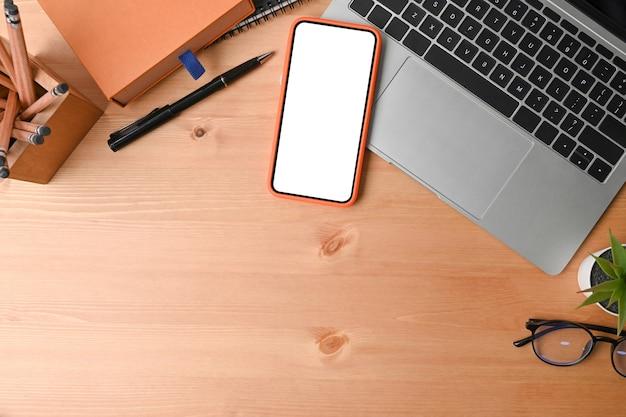 Vue de dessus du téléphone portable, de l'ordinateur portable, du porte-crayon et du cahier sur fond en bois.