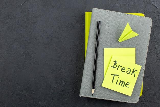 Vue de dessus du temps de pause écrit sur des notes collantes au crayon noir sur des blocs-notes sur un lieu de copie de table sombre