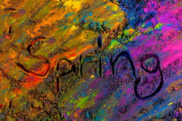 Vue de dessus du texte de printemps manuscrit sur poudre de holi multicolore