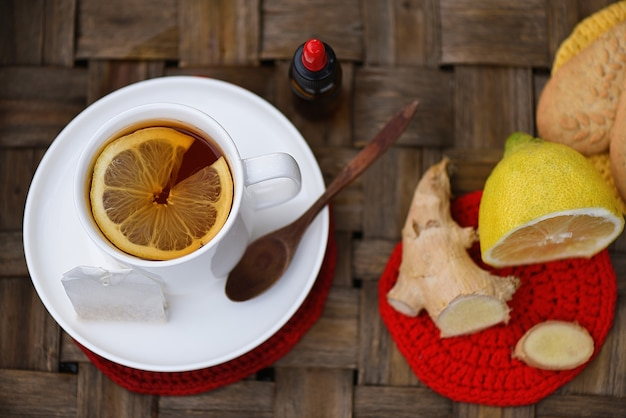 Vue de dessus avec du thé chaud avec des gouttes de citron, de gingembre et de propolis