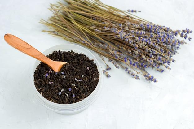 Vue de dessus du thé noir avec des pétales de lavande et un bouquet de lavande séchée sur fond blanc minable