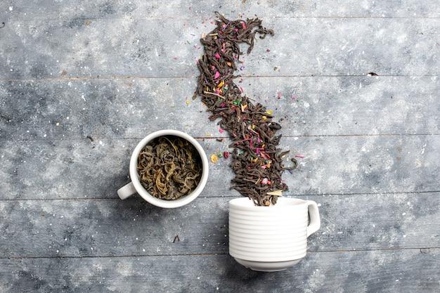 Vue de dessus du thé séché frais à l'intérieur et à l'extérieur de la tasse sur l'espace rustique gris