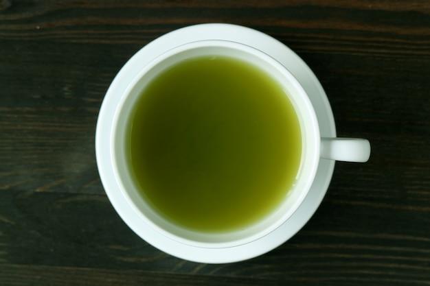 Vue de dessus du thé vert matcha chaud de couleur verte vibrante sur une table en bois brun foncé
