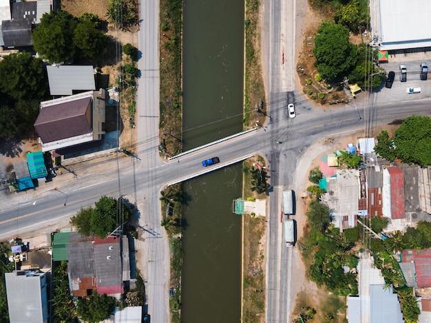 Vue de dessus du trafic sur la route d'intersection à travers le pont sur le canal dans un village rural