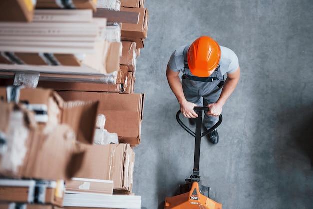 Vue de dessus du travailleur masculin dans l'entrepôt avec transpalette.