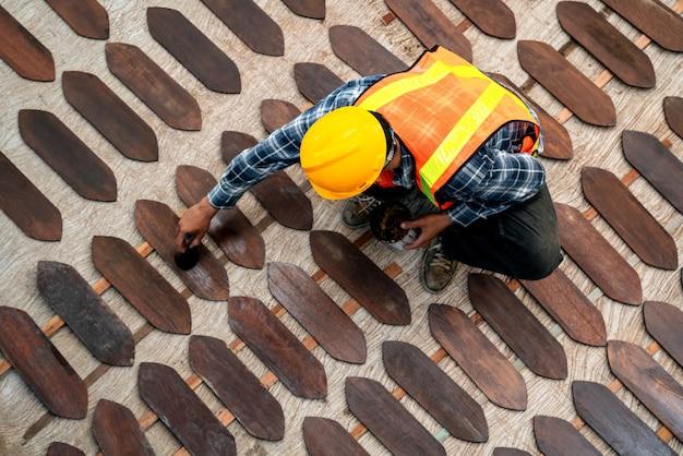 Vue de dessus du travailleur peignant ou vernissant sur une planche de bois sur un chantier de construction.