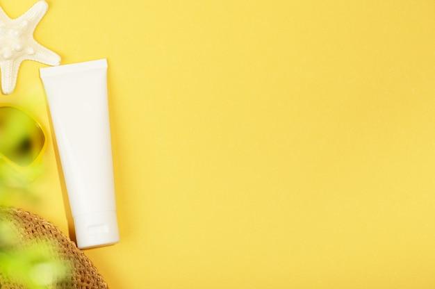 Vue de dessus du tube blanc sans marque, étoile de mer, lunettes de soleil et plante verte. tube vierge pour crème solaire, lotion hydratante ou crème nutritive. style de maquette, isolé sur fond jaune. cosmétiques naturels.