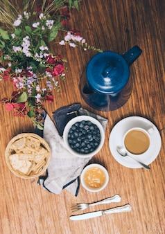 Une vue de dessus du vase; myrtilles; des craquelins; confiture; tasse à café et théière sur fond en bois
