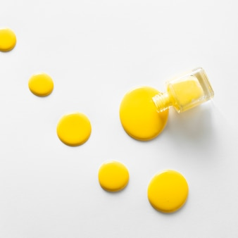 Vue de dessus du vernis à ongles jaune sur fond blanc