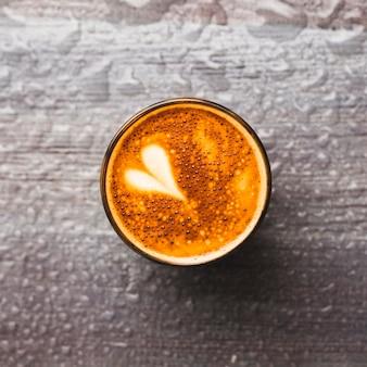 Vue de dessus du verre de café savoureux avec art au latte sur fond de goutte d'eau