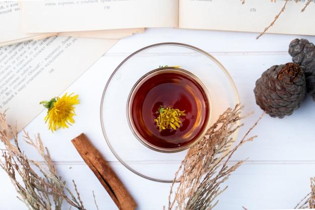 Vue de dessus du verre de thé armudu avec des pissenlits, des bâtons de cannelle sur blanc