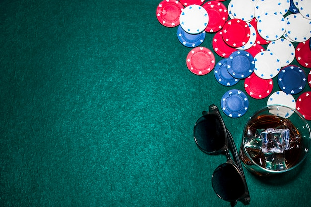 Vue de dessus du verre à whisky; lunettes de soleil et jetons de casino sur la table de poker