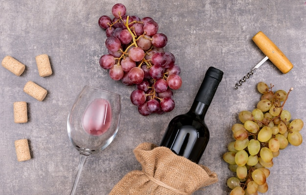 Vue de dessus du vin rouge dans un sac en toile avec verre et raisin sur pierre sombre horizontale