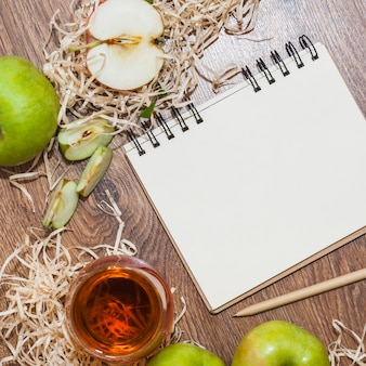 Une vue de dessus du vinaigre de cidre de pomme; pommes vertes et bloc-notes en spirale avec un crayon sur un bureau en bois