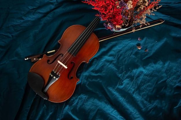 Vue de dessus du violon et de l'archet mis à côté du pot de fleurs séchées