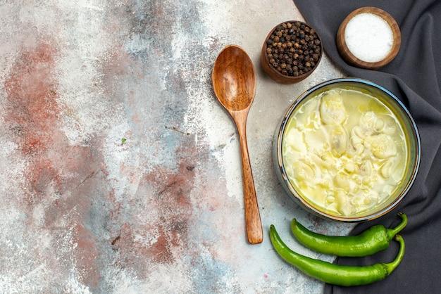 Vue de dessus dushbara une cuillère en bois torchon noir bols de piment avec du sel de poivre noir sur une surface nue avec copie espace