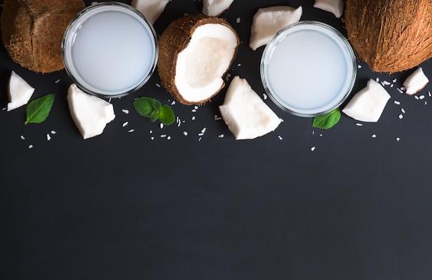 Vue de dessus de l'eau de coco dans deux verres et ingrédients sur un fond sombre
