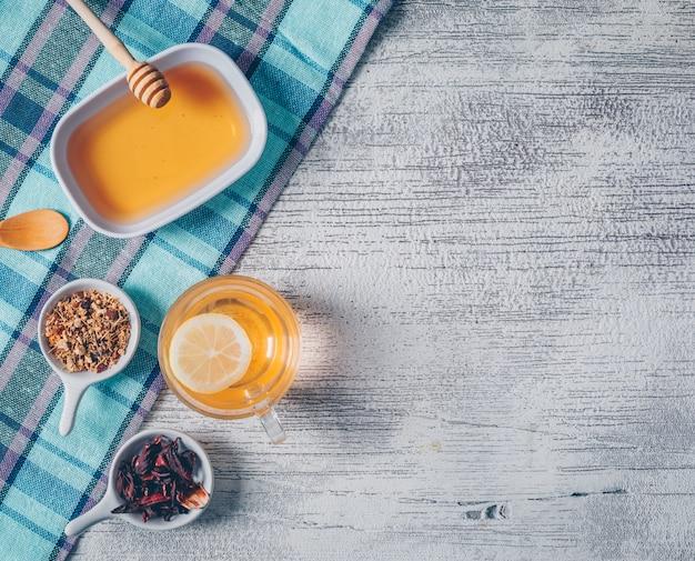 Vue de dessus de l'eau de couleur orange avec du miel et des herbes de thé sur un tissu de pique-nique et un fond en bois gris. espace horizontal pour le texte