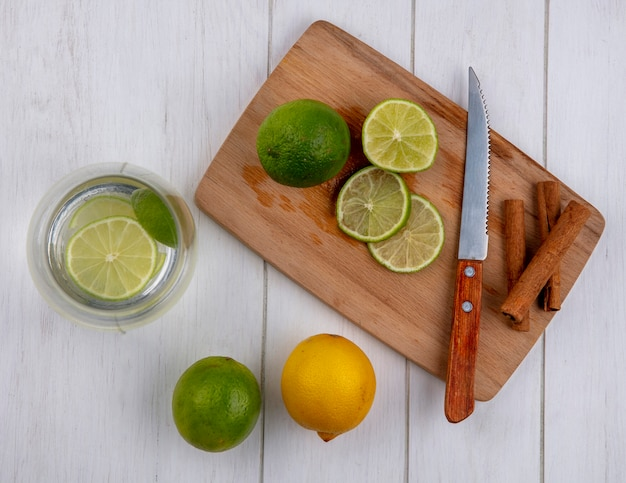 Vue de dessus de l'eau dans un verre avec de la chaux et du citron sur une planche avec un couteau et de la cannelle sur un tableau blanc