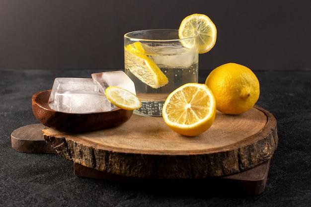Une vue de dessus de l'eau avec du citron boisson fraîche fraîche à l'intérieur du verre avec des glaçons avec des citrons en tranches sur le fond sombre boisson cocktail fruit