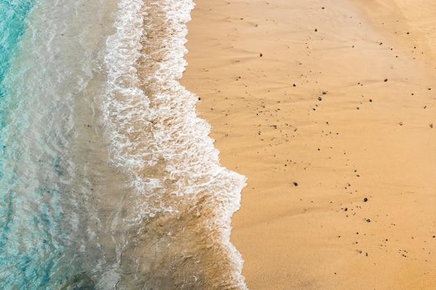 Vue de dessus de l'eau de mer touchant le sable sur la rive
