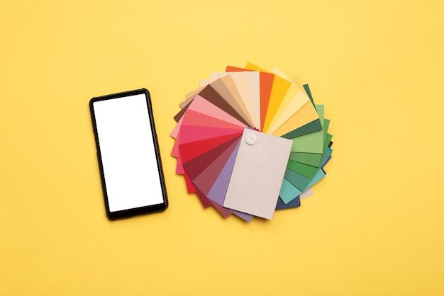 Vue de dessus des échantillons colorés et smartphone avec écran blanc sur fond jaune.
