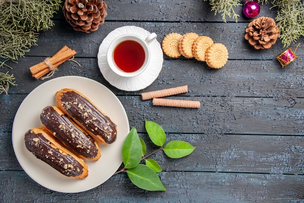Vue de dessus éclairs au chocolat sur cônes de plaque ovale blanche jouets de noël sapin feuilles de cannelle et différents biscuits sur un sol en bois foncé avec des espaces de copie