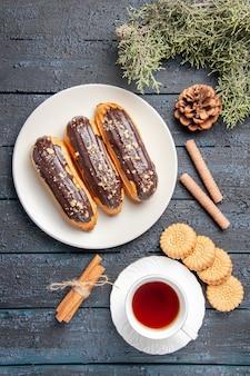 Vue de dessus éclairs au chocolat sur plaque ovale blanche cône sapin feuilles cannelle différents biscuits et une tasse de thé sur un sol en bois foncé