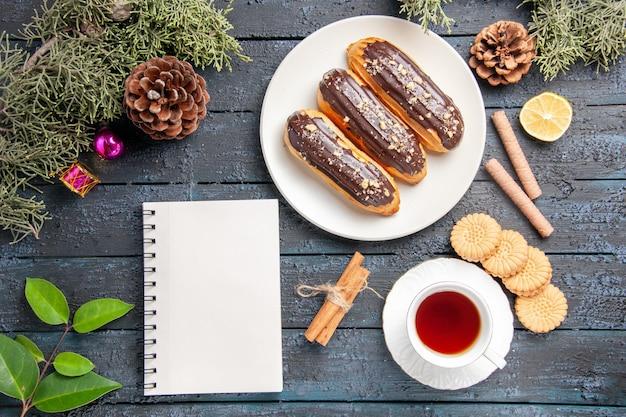 Vue de dessus éclairs au chocolat sur plaque ovale blanche cônes feuilles de sapin jouets de noël tranche de cannelle de citron différents biscuits une tasse de thé et un cahier sur un sol en bois foncé