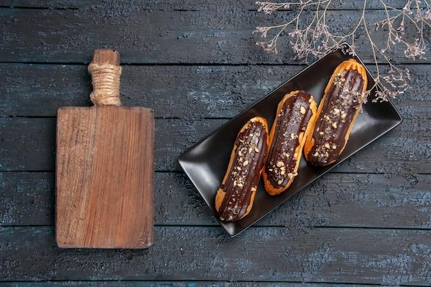 Vue de dessus des éclairs au chocolat sur une plaque rectangulaire et une planche à découper sur la table en bois sombre avec de l'espace libre
