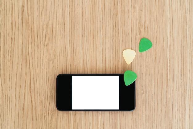 Vue de dessus de l'écran du smartphone avec un contenu vierge. étudier et apprendre le concept en ligne de leçons de guitare. explorez la musique et la technologie ensemble. médiators et espace de copie de téléphone à écran blanc.